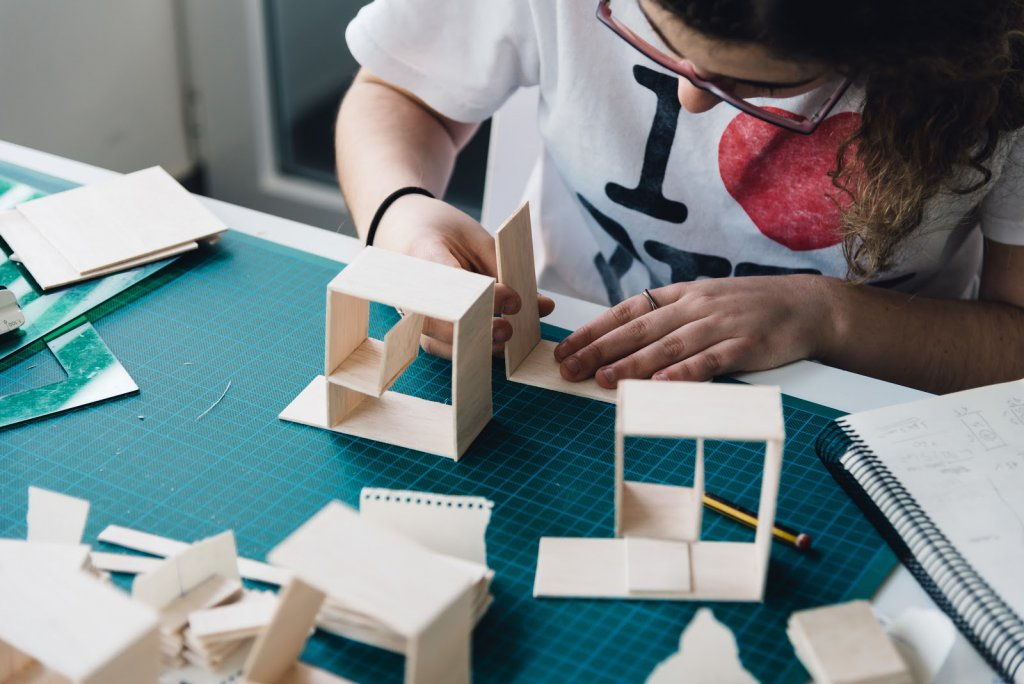 Woman architecture student working on models