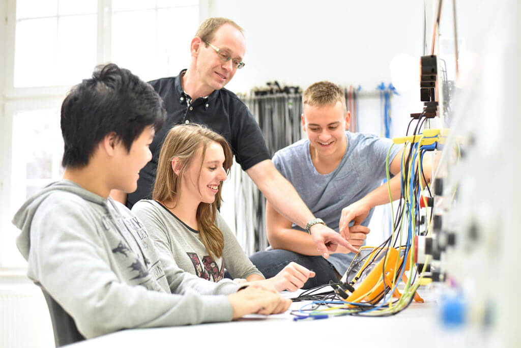 engineering teacher engaging with students in lab