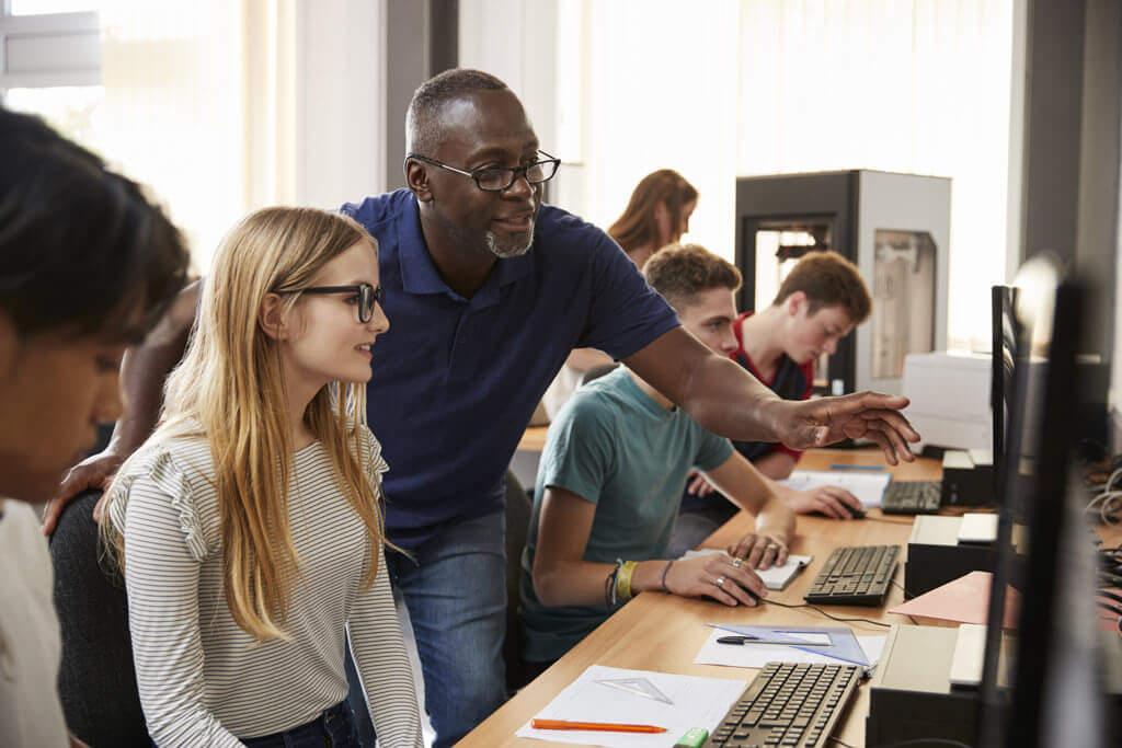 engineering teacher helping student in 3d printing lab